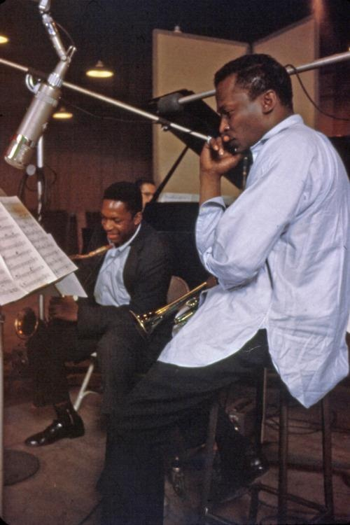 A laughing John Coltrane and a pensive Miles Davis during recording.