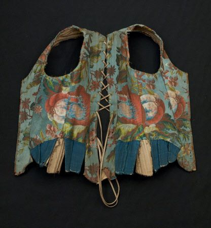 """Part of corset bodice and sleeves - Made from blue silk brocade with a large scale design of naturalistic flowers in pinks, greens and yellows. This is French silk - point rentree 1735-1737. There are blue linen tabs. It is lined with linen. It is heavily boned with eyelet holes down the backs and fronts for the stomacher. Sleeves would attach with blue ribbon. The cuff of the sleeves is trimmed with cream silk ribbon. There are 6 hip tabs. (female) (foundation garment)"""