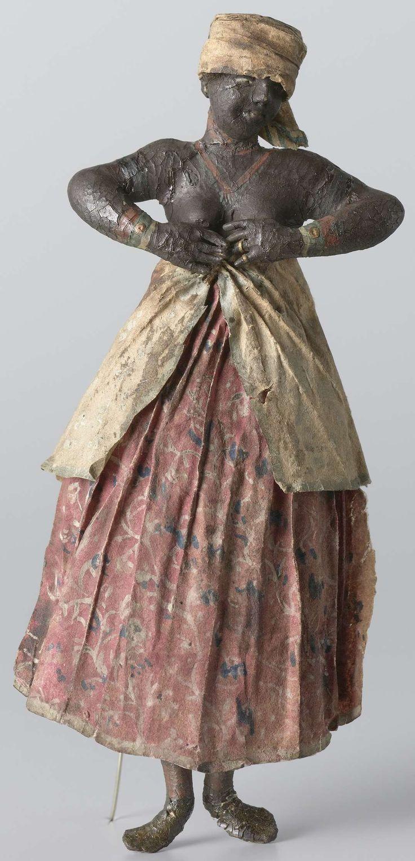 Gerrit Schouten | Een Creoolse, Gerrit Schouten, c. 1810 - in or before 1839 | Een los figuur uit een diorama van Gerrit Schouten, voorstellende een Creoolse vrouw, staand. Haar beide handen voor haar borsten houdend. De vrouw draagt een lange geplooide rok, rood met een bloemmotief in blauw en wit. Over deze rok draagt ze een witte effen omslagdoek (pangi). Ze draagt armbanden, een ketting en een hoofddoek Haar bovenlichaam is onbedekt. Ze is blootvoets.