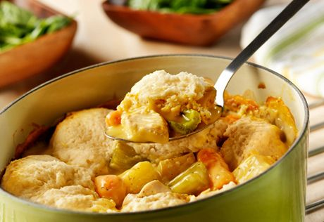 The slow cooker simmers chicken, potatoes, carrots, and celery in a creamy sauce, topped with tender dumplings made easy and delicious with baking mix.