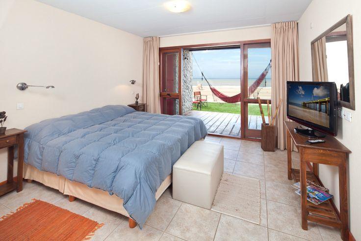 Dormitorio de hotel con vistas y acceso a la playa.