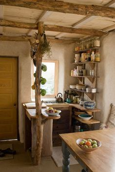 Few natural resources consumed in the construction of this tiny kitchen.  Small logs for posts and beams, stucco walls, open shelving.