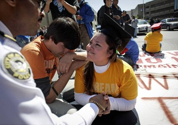 illegal immigrant Virdiana Martinez, right, is comforted by activist Mohammad Abdollahi, as Major K. E. Williams, left, of the Atlanta Police Department warns her of arrest unless she moves while protesting for rights for higher education for illegal immigrants in Atlanta. When Williams informed her she could get up now and that she's made her point, Martinez asked him if his ancestors had that opportunity.