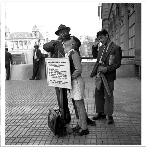 """Ambulante e suas """"maravilhas do mundo"""" no Viaduto do Chá, na década de 1940. Podemos ver do lado esquerdo o Palacete Prates que era sede do Automóvel Clube e do lado esquerdo a lateral do """"prédio da Light"""". Acervo Jean Manzon."""