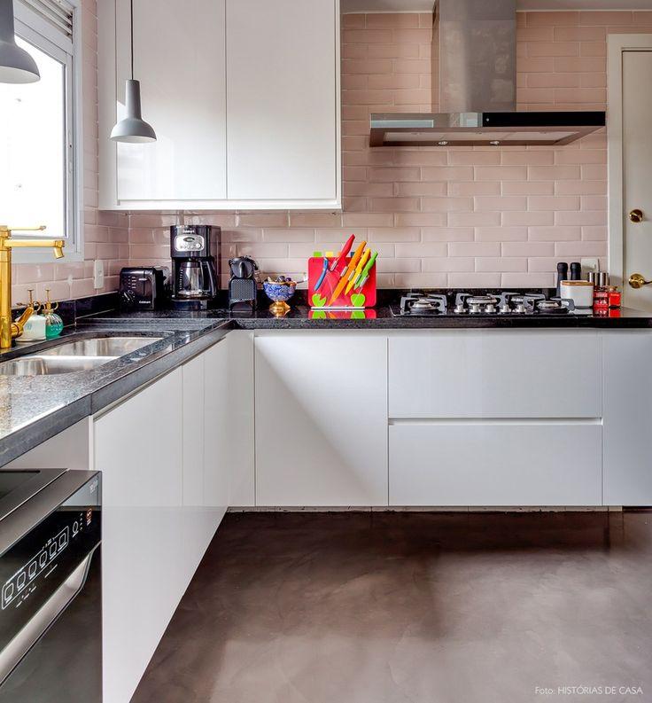 Uma cozinha com azulejos rosa, bancada de granito preto e torneiras tingidas de dourado