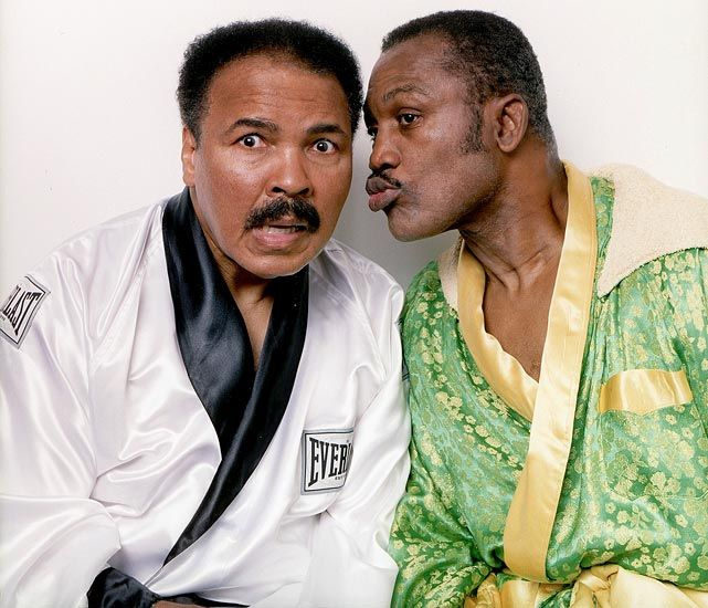 Joe Frazier leans in toward Muhammad Ali, both posing in boxing robes they wore the night of their first bout, during a photo shoot at Frazier's Gym in Philadelphia on Oct. 2, 2003. Smokin' Joe, who passed away on Nov. 7, 2011, would have celebrated his 70th birthday today (Jan. 12, 2014). (Walter Iooss Jr./SI)