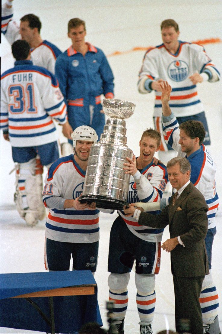 Edmonton Oilers team captain Wayne Gretzky, right, and Mark Messier hold up the Stanley Cup trophy following the team's 6-3 win over the Boston Bruins in the Stanley Cup hockey finals in Edmonton, Alberta, Canada, May 26, 1988. (AP Photo/Rusty Kennedy)