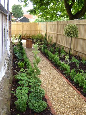 Just a thought - but perhaps the side garden needn't have raised beds but formal beds like this?