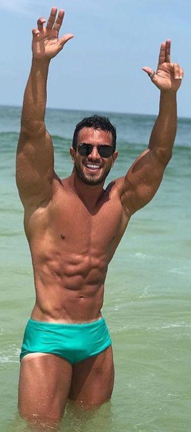 7791ff9457e Bella sonrisa de musculoso y paquetudo galán en la playa en bikini ...