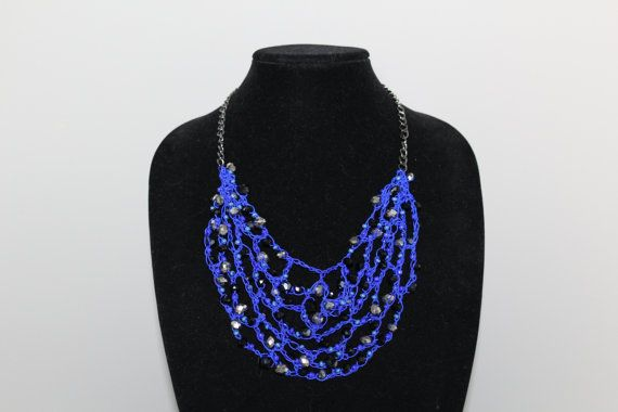 Hand made crochet bib necklace in cobalt blue nylon crochet thread adorned with multi-colour black, silver and blue beads. Necklace is on a