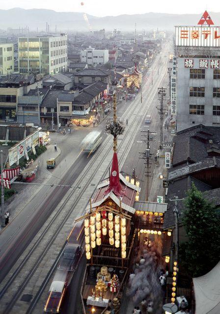 1960年7月16日、前祭の宵山を四条烏丸の旧三和銀行屋上から西向きに撮影。ビルは少なく、町家が並ぶ。四条通には市電の軌道も延びる。手前に函谷(かんこ)鉾、奥に月鉾が見える