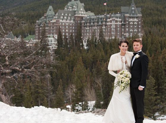 the lovebirds pose on a snow-covered mountaintop in front of the majestic Fairmont Banff Springs Hotel (the venue where they got married). T...