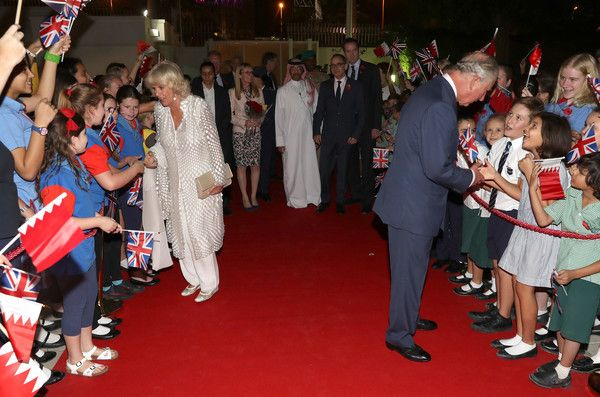 Prince Charles, Prince of Wales (R) and Camilla, Duchess of Cornwall are greeted by schoolchildren as they attend a reception at the British Embassy on November 10, 2016 in Manama, Bahrain.