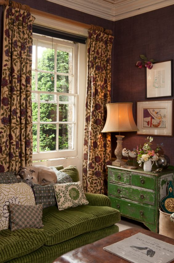 Lovely use of green in a George Smith wide wale corduroy sofa, mixed color crewel draperies and distressed green chest of drawers.