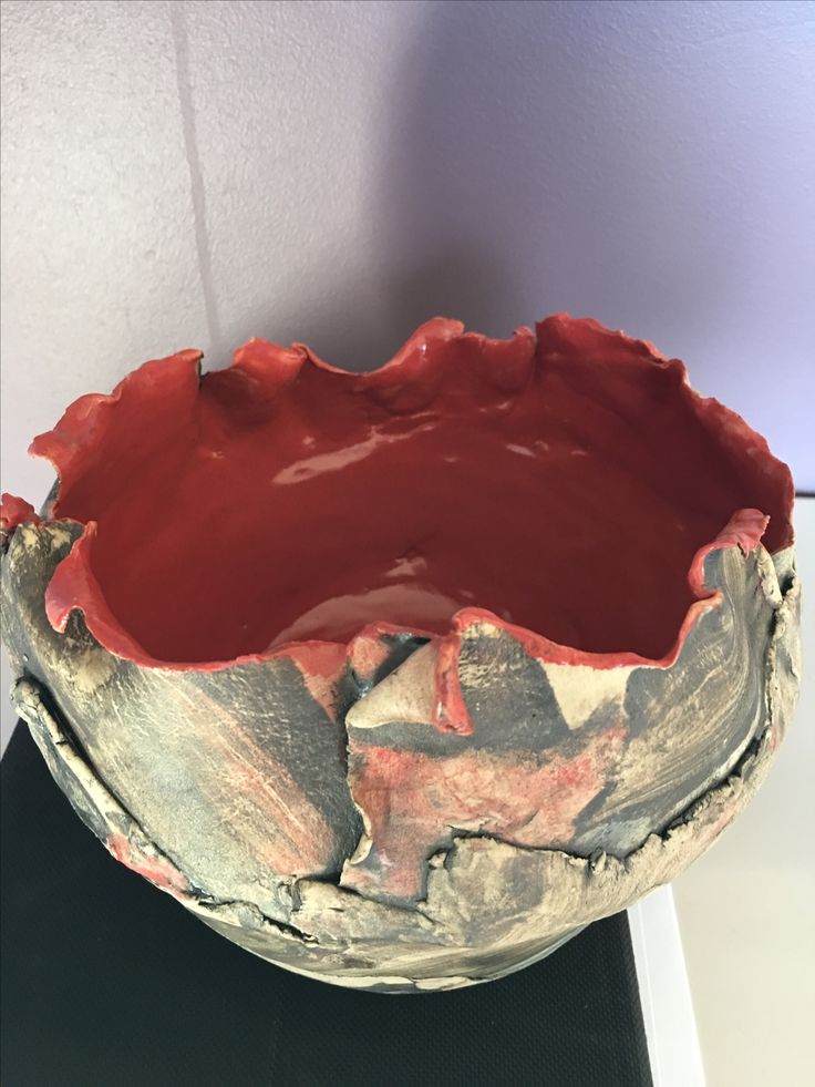 Ceramic bowl made with pieced coloured clay strips. Brick red glaze inside.