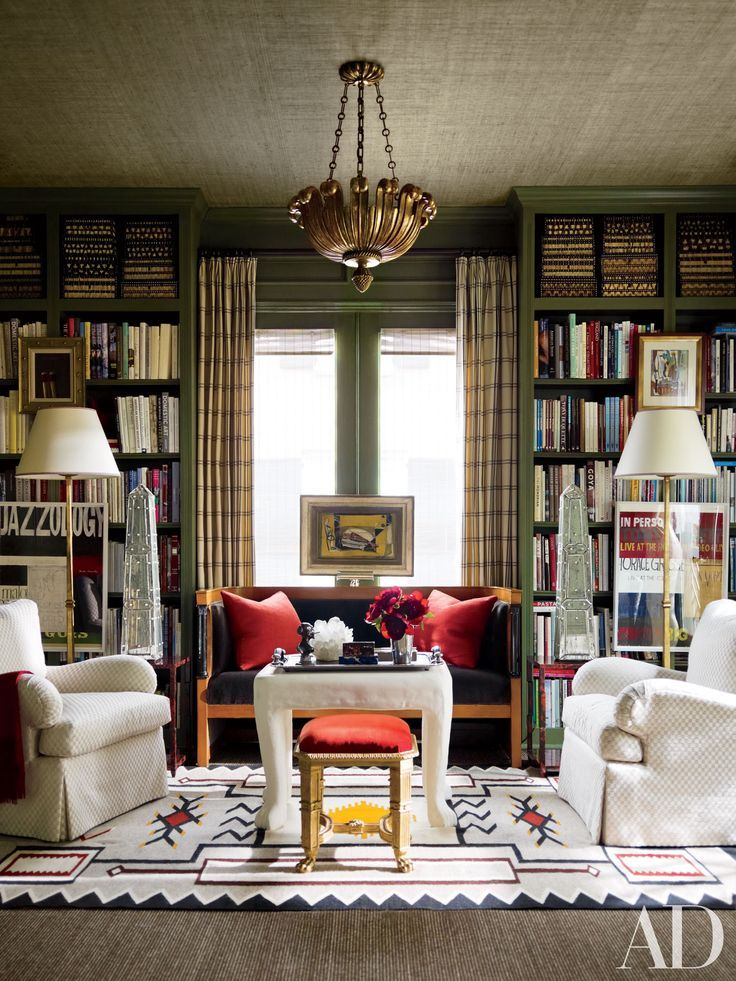 In the library of Houston decorator J. Randall Powers's home, a Paul Ferrante ceiling fixture is suspended above a Cubist painting by Michel Patrix and a Biedermeier settee from Karl Kemp Antiques.