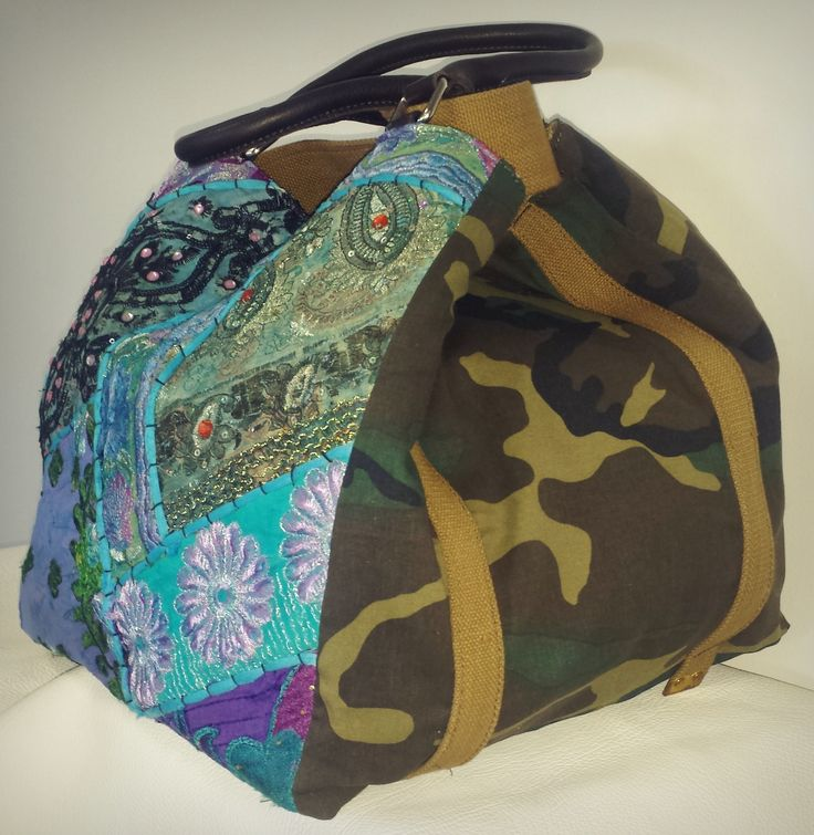 Borsa da spalla reversibile, dotata di quattro manici due in pelle e due in tessuto originali militari. Decorata al frontale in tessuto indiano batik patchwork.  Misure: 32.5x30x30  Handbag made of twisted genuine leather garment dyed. Decorated with studs and an external pochet on the  rear. Equipped with shoulderbelt and available in grey and leather. Measures: 32.5x30x30