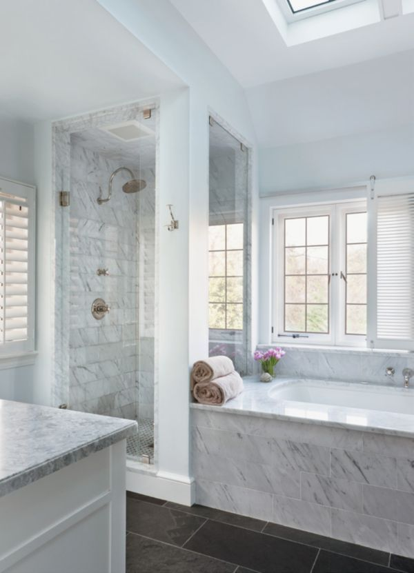 """The owners wanted their master bathroom to be """"a quiet, soothing space,"""" Welch says. She responded with dark slate floors and Carrara marble from Architectural Ceramics. Architect Stephen Muse created multiple light sources with windows and skylights, and designed a special glide system for the shutters over the tub to ensure privacy."""