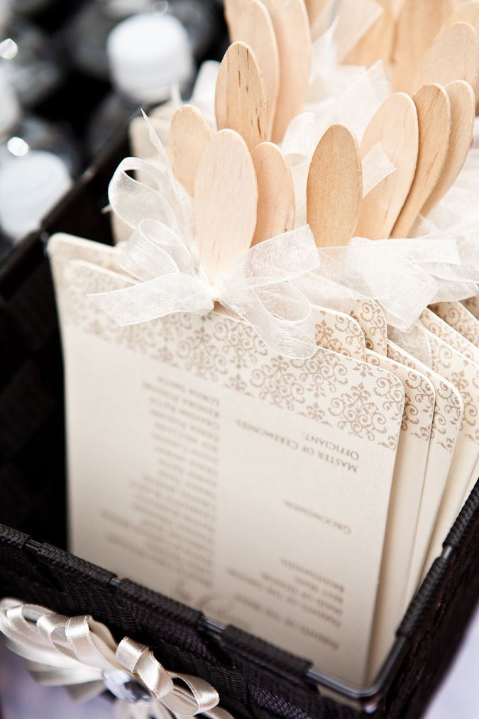 My wedding-Program fans-Parchment paper with silvery/metallic *with a hint of peach* print/design over hard antique-white paper. Handles sprayed antique-white to match program paper, finished with see-through coral ribbon in a bow.