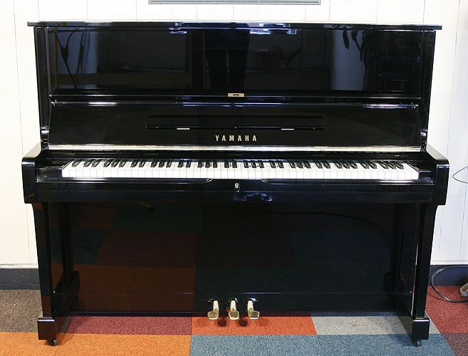 a 1960 yamaha u1 upright piano with a black case and