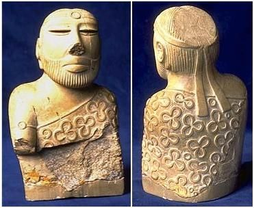 """Figure 9-4 Torso of a """"Priest King"""" Pg. 294 S.L  This figure was from Mohenjo-Daro in 2600-1900 BCE and it was known as the male torso but sometimes called the """"Priest-King"""". Priests were function as kings. The man's garment is patterned with trefoil. This man was made out of stone."""