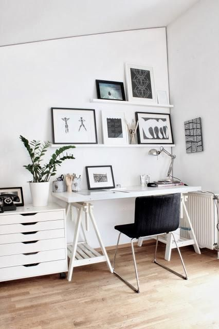 shelves, white, black, and grey wooden flooring framed pictures table plant white table and black chair