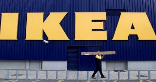 An employee of an IKEA store in the  northern Greek town of Thessaloniki carries furniture parts December 4, 2002. [Police sealed off 10 IKEA stores in the Netherlands after bombs found in two branches of the world's biggest furniture retailer were difused at the start of the busy Christmas shopping season.] - RTXLO1R