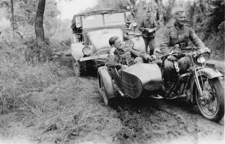 German soldiers on captured Soviet motorcycle TIZ AM-600 on a forest road. In the background a Krupp Protze, L2H43/143 heavy lift half truck.