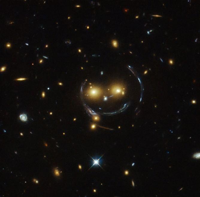 """C'è uno smile tra le stelle, la gravità disegna con la luce! Lo """"smile"""" e i contorni di questa faccia che ci 'sorride' da miliardi di anni luce di distanza sono stati, per così dire, disegnati dai due 'occhi' al centro del cerchio: l'ammasso stellare SDSS J1038+4849, fotografato in questa recente immagine dal telescopio spaziale Hubble."""