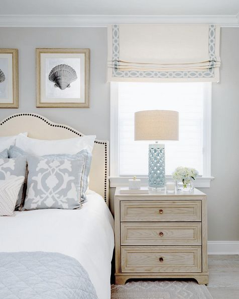 An elegant bedroom in soft blues designed by Leedy Interiors features a neutral linen roman shade edged with Ogee Embroidered Border from Samuel & Sons