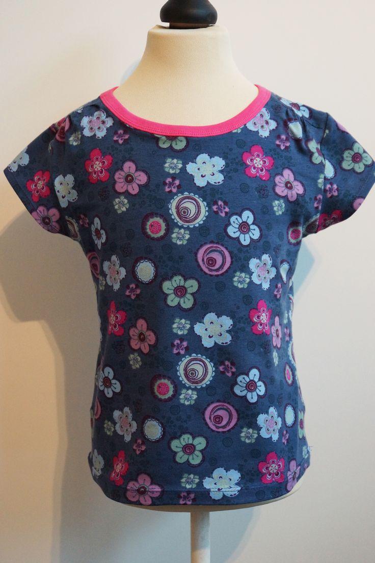 Sunny Flowers van Qjutie Kids is een mooie tricot met bloemen. De hals is afgewerkt met fuchsia roze boordstof.