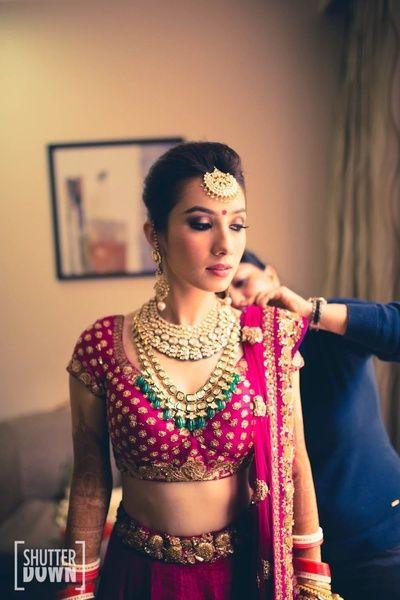 deep maroon bridal lehenga , contrast jewellery , emerald and polki necklace , ruby pink bridal lehenga  ,magenta blouse , maang tikka , polki necklace