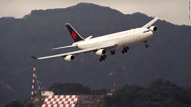 """In the background is the famous Checkerboard Hill. The orange and white checkerboard served as a visual signal for pilots to begin the turn for the Hong Kong runway. The maneuver became known as the """"checkerboard turn."""""""