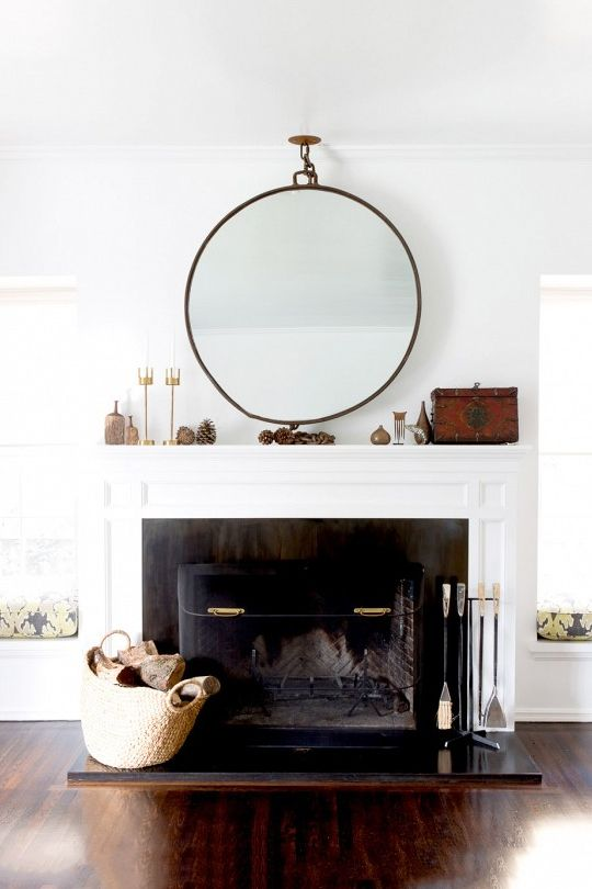 giant circular mirror above black and white fireplace