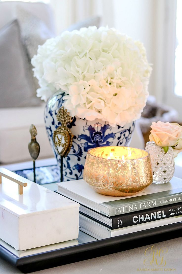Fabulous coffee table tray with sacred hearts, ginger jar with hydrangeas, marble box, mercury glass votive candle, and pretty books. Transitional Family Room Reveal - Randi Garrett Design