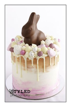 Vanilla Cake, with Easter Drip Cake buttercream Neapolitan watercolor swirl. with Easter embellishments, chocolate eggs and chocolate drizzle drip. Topped with a Lindt chocolate bunny