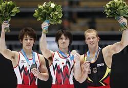 体操世界選手権の男子個人総合で前人未到の4連覇を達成、表彰台でメダルを掲げる内村航平。左は2位の加藤凌平、右は3位のファビアン・ハンブッヘン=3日、ベルギーのアントワープ(共同)