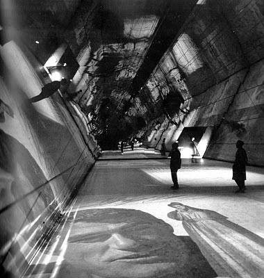 La Sala del Caleidoscopio, ricavata nel salone d'ingresso della Triennale. A questo ultimo grande ambiente si accedeva da una porta triangolare alquanto originale. Si apriva così uno spazio piramidale, trasformato in sala per proiezioni cinematografiche. Le pareti erano state completamente rivestite di specchi su tutta l'altezza (più di 10 metri): le due testate si specchiavano luna nell'altra moltiplicando all'infinito la dimensione reale dello spazio, mentre le pareti laterali producevano…