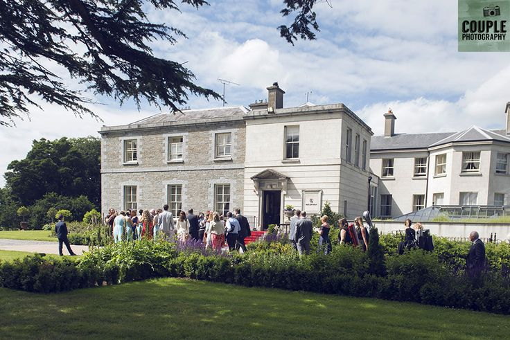 Guests mingle in the summer dun. Weddings at Tankardstown House by Couple  Photography.