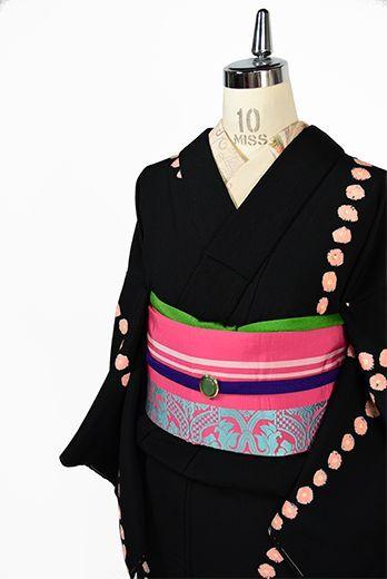 シックな黒をベースに、ふわりと浮かぶパウダーコーラルピンクの本絞り水玉模様が形作るモダンパターンが印象的な正絹縮緬の袷着物です。
