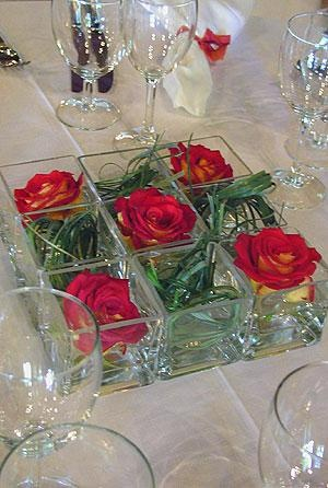 Twisted bear grass in square, glass containers with red roses. Ideal design for centre piece or for a long table or mantel.
