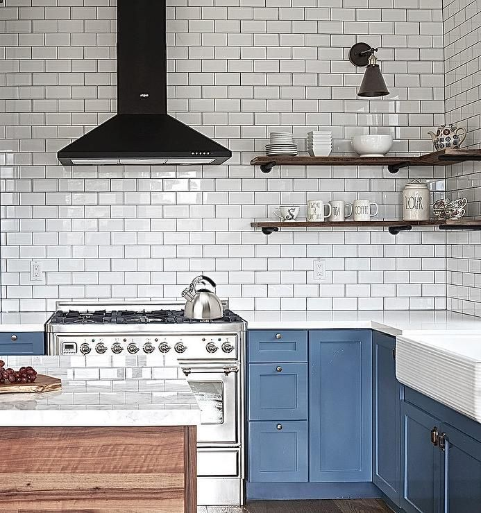 Blue and white contemporary kitchen boasts rustic accents with a plank island topped with a white and gray marble countertop and stacked wood wraparound shelves positioned in a corner beneath a bronze sconce and beside a black hood.