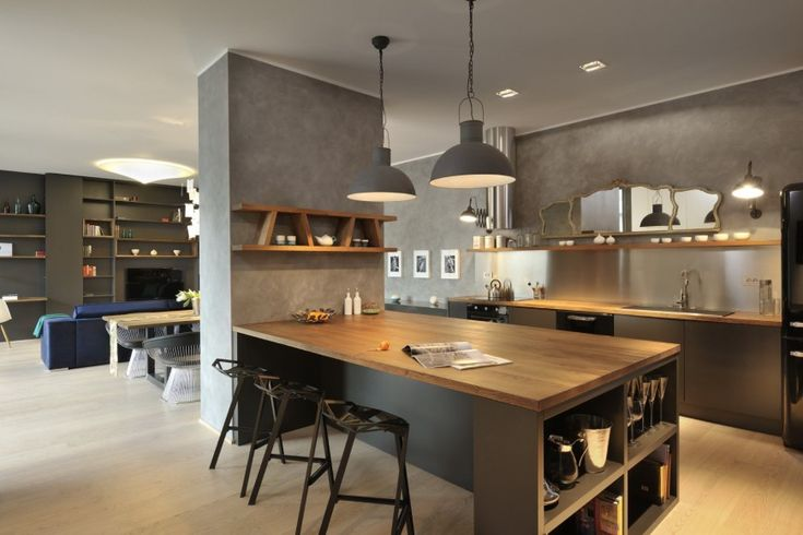 As we pull back a bit, the large central countertop is revealed, with bar style seating on outer side, built-in shelving, and central dividing wall with wood shelves overhead.