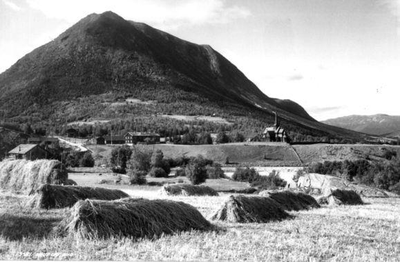 DigitaltMuseum - Lom stavkirke og prestegård, Oppland 1935. Gårdsanlegg i forgrunnen. Høyonn. Fjell i bakgrunnen.