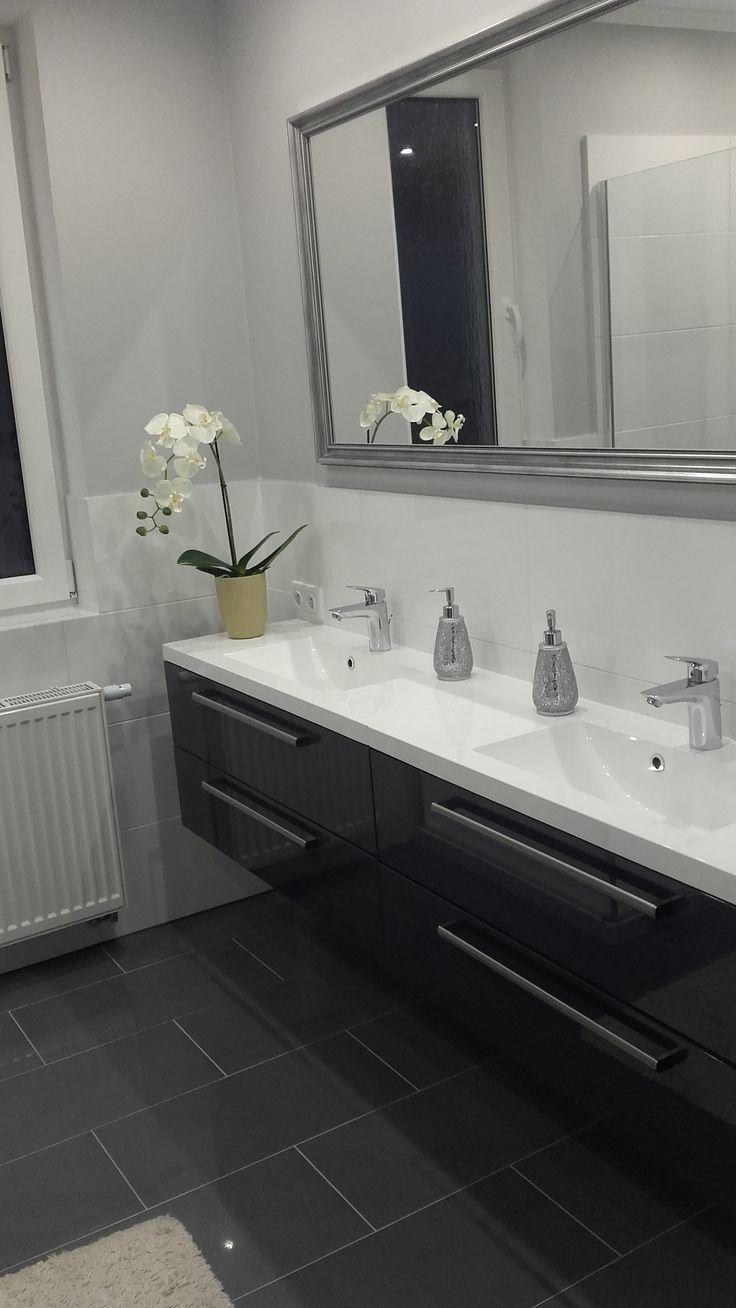 Lustro w ozdobnej ramie optycznie powiększa pomieszczenie i pieknie kompomnuje się z połyskiem szafki łazienkowej Athos.