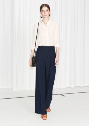 Breezy and graceful tailored trousers with creased wide legs, and a concealed zip closure on the side of hip.