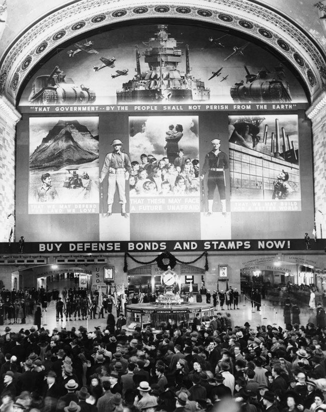 In wartime: The main concourse is crowded with people on Dec. 14, 1941, during the unveiling of a government mural above the mezzanine level that encouraged Americans to buy savings bonds and stamps in support of the war. Down the hallway to the right, an archway points travelers toward the nearest telegraph — how quaint!