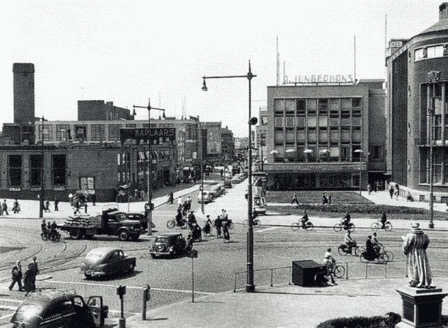 """""""Van Hogendorpsplein"""" (1954) Direkt na de oorlog betrok Jungerhans een nieuw pand, nagenoeg op dezelfde locatie.... en dat alles t.g.v. 14 mei 1940.  De naam is dan allang weer ingetrokken, een klein gedeelte van het vroegere Van Hogendorpsplein heet nu Schielandstuin. De naam Boijmansstraat werd trouwens veranderd in Bulgersteyn. Rechts beeld van Erasmus."""
