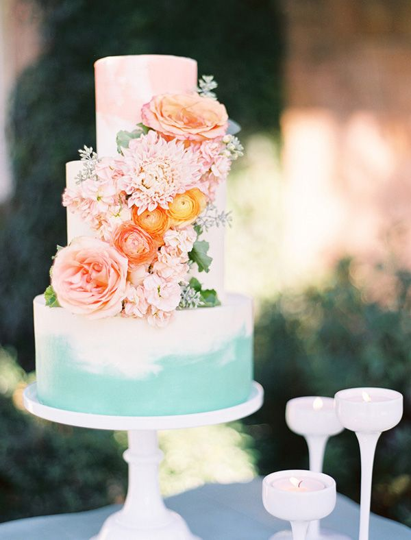 Soft coral and teal brushwork takes a simple tiered cake from ordinary to extraordinary. Cascading flowers add an ombre-inspired pop of colour.