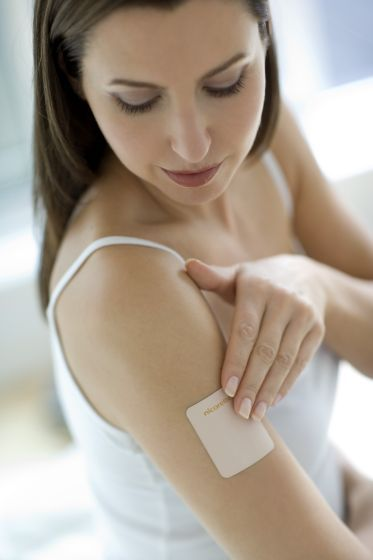 image #00djyc15 Nicotine patch on a woman's arm. Nicotine is an addictive drug found in cigarettes. When the patch is applied to the surface of the skin, the nicotine in the patch is released in small measured doses into the bloodstream. A course of patches slowly decreases the amount of nicotine delivered, easing the withdrawal symptoms felt by smokers who are trying to quit. #photo #image #tabac #traitement #arreterdefumer #femme